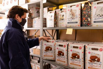 A person in a face mask picks out a soft craft kit from a shelf
