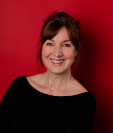 Jo Lochhead smiles at the camera in front of a red background