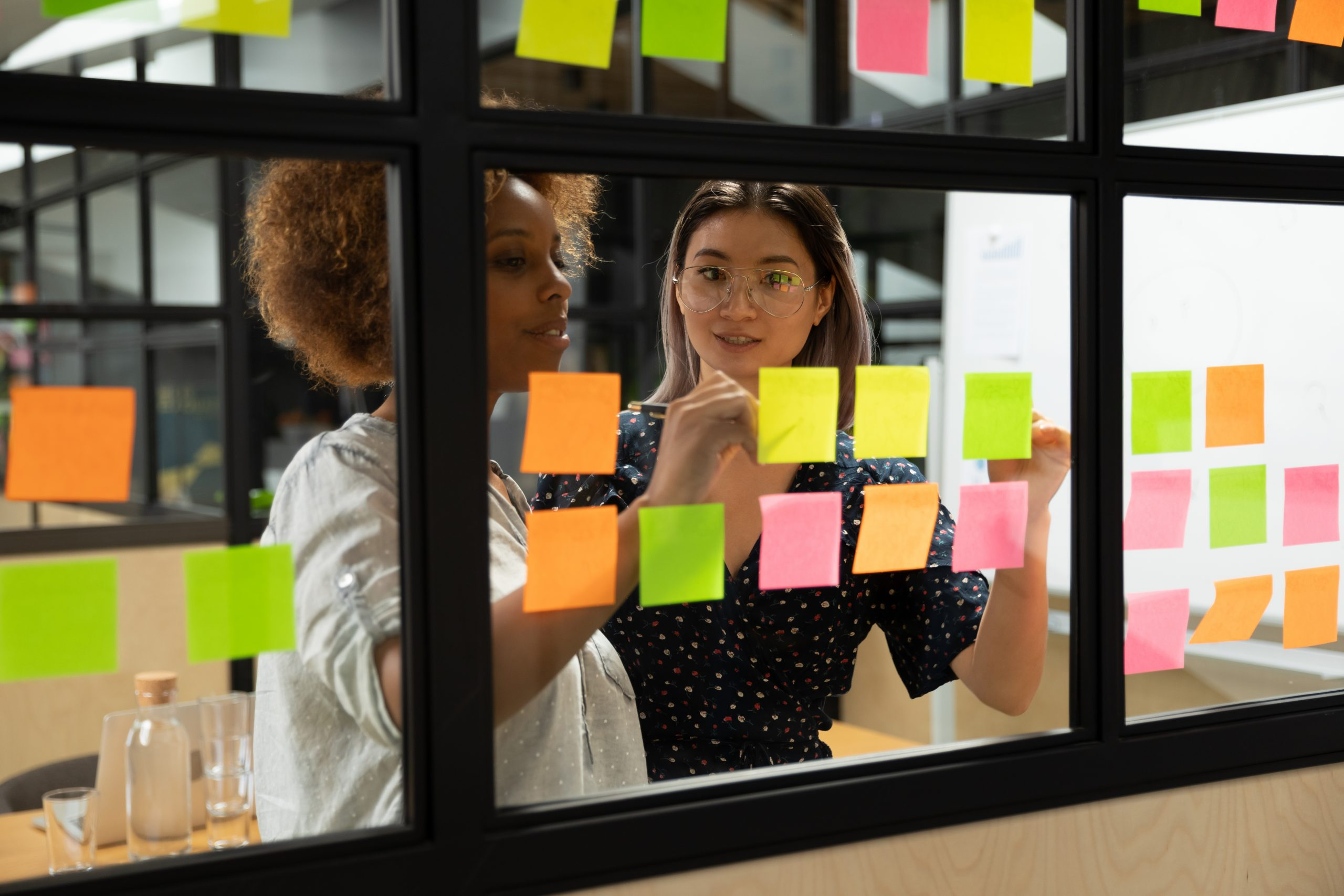 Two women work together with post-it notes on a board