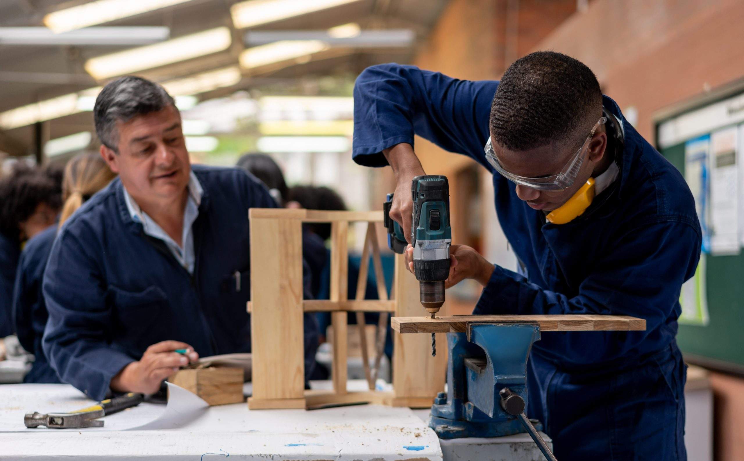 A young man drills a piece of wood while a tutor looks on