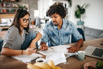 A man and a woman discuss finances at a table