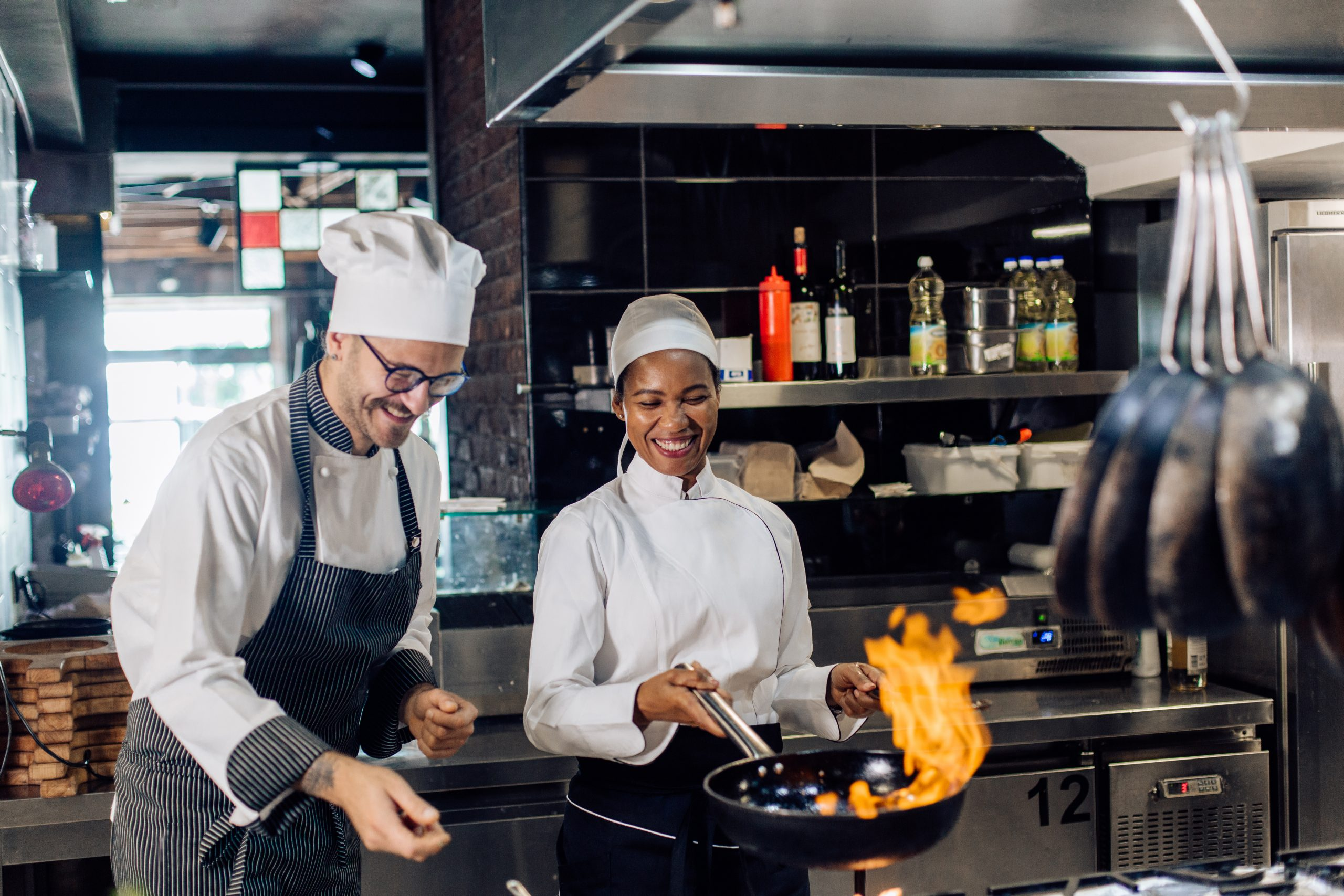 Female chef tossing a saucepan with a supervisor